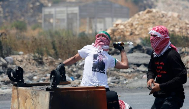 A Palestinian man throwing a Molotov cocktail at Israeli soldiers, during clashes in the west Bank city of Ramallah, Monday, July 24, 2017
