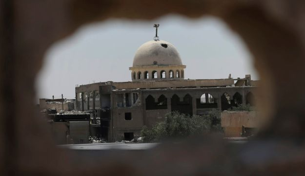 A destroyed mosque is seen through a hole of U.S.-backed Syrian Democratic Forces sniper, on the front line on the eastern side of Raqqa, Syria, July 26, 2017.