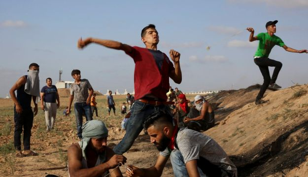 Protesters throw stones at Israeli solders during clashes on the border with the Gaza Strip, July 28, 2017.