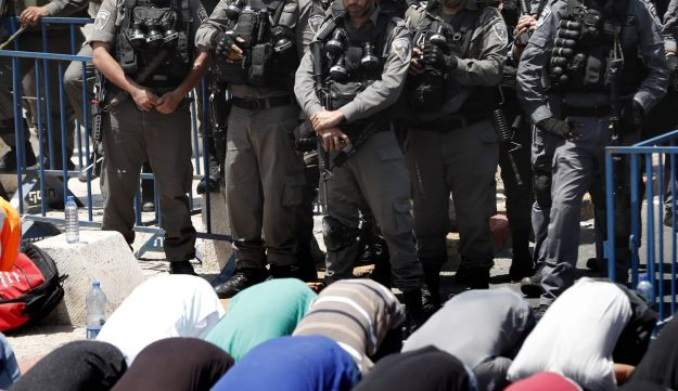 Israeli border guards keep watch as Palestinian Muslim worshippers pray outside Jerusalem's Old City overlooking the Al-Aqsa mosque compound. July 28, 2017