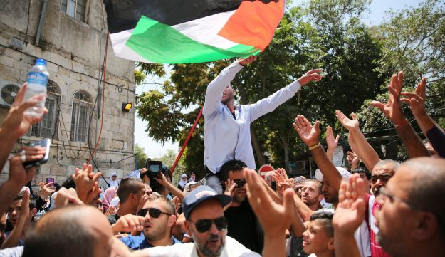 Palestinians celebrate at the Lions Gate in Jerusalem after Israel removes security restrictions implemented on Temple Mount, July 24, 2017.