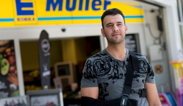 Omer Unlu stands in front of the supermarket in Hamburg, Germany on Monday, July 31, 2017 where he and other pedestrians stopped the attacker who fatally stabbed one person and wounded six others.