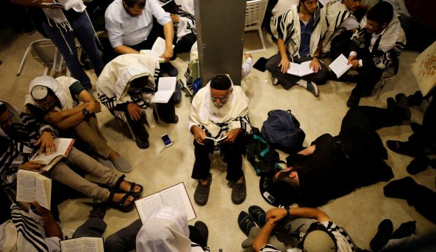 Jewish worshippers pray next to the Western Wall on Tisha B'Av, a day of fasting and lament, in Jerusalem's Old City August 1, 2017.