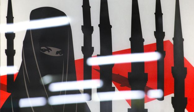 A campaign posters of the far-right Swiss People's Party depicting a woman wearing a burqa against a background of a Swiss flag upon which several minarets resembling missiles October 26, 2009 in Zurich.
