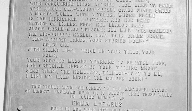 "FILE- In this circa 1950 photo shows a bronze plaque of the poem by Poet Emma Lazurus on Statue of Liberty in New York. In 1903, the poem was engraved on the bronze plaque and mounted inside the pedestal's lower level. Senior White House aide Stephen Miller told reporters Wednesday, Aug. 2, 2017, that the poem written by Emma Lazarus about the ""huddled masses"" is not part of the original Statue of Liberty. Miller says the Statue of Liberty is a ""symbol of American liberty lighting the world"" and suggested the statue had little to do with immigrants. (AP Photo/File)"