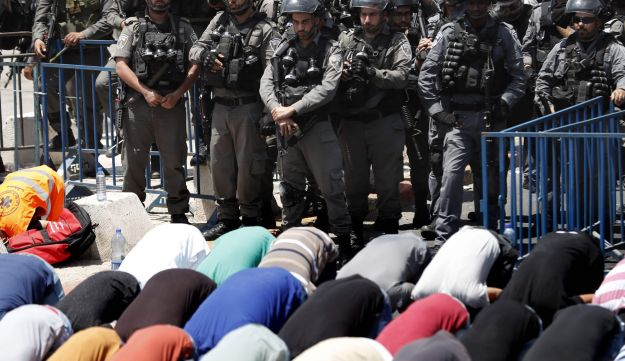 Israeli border guards keep watch as Palestinian Muslim worshippers pray outside Jerusalem's old city overlooking the Al-Aqsa mosque compound on July 28, 2017.