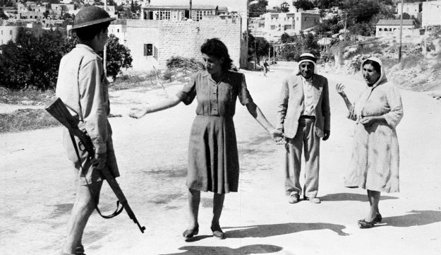 An Israeli soldier, armed with a rifle, stop some arabs in a street in Nazareth, Palestine, July 17, 1948, as they are travelling after the allotted curfew time.
