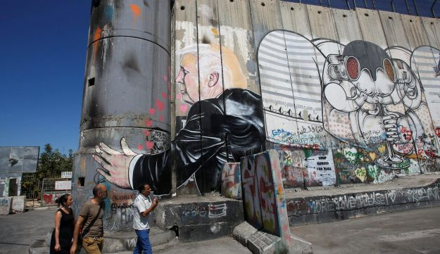 Tourists stand in front of a graffiti depicting U.S President Donald Trump on the controversial Israeli barrier in the West Bank town of Bethlehem August 4, 2017.