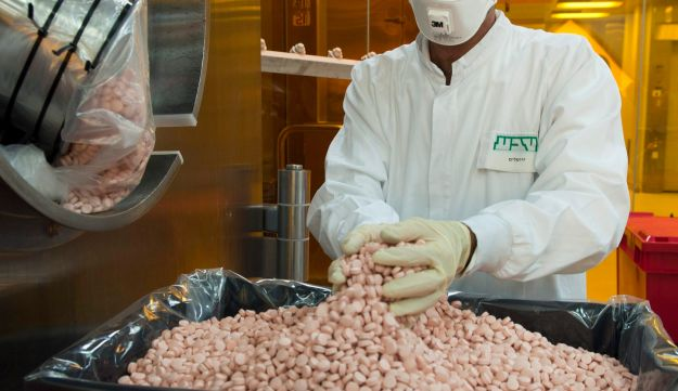 An employee collects newly manufactured pills from a machine at the tablet production plant at Teva Pharmaceuticals' headquarters in Jerusalem, September 19, 2011.