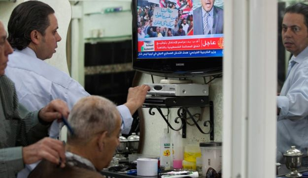 A Palestinian barber gives a customer a haircut as a TV set shows a demonstration in Egypt, on the Al Jazeera channel, at a barber shop in Jerusalem's Old city on May 4, 2011.