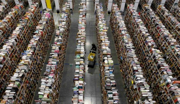 A worker gathers items for delivery at Amazon's distribution center in Phoenix, Arizona, November 22, 2013.