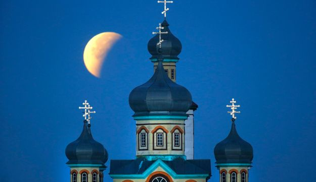 Supermoon is seen at the finish of a lunar eclipse behind an Orthodox church in Turets, Belarus. Sep
