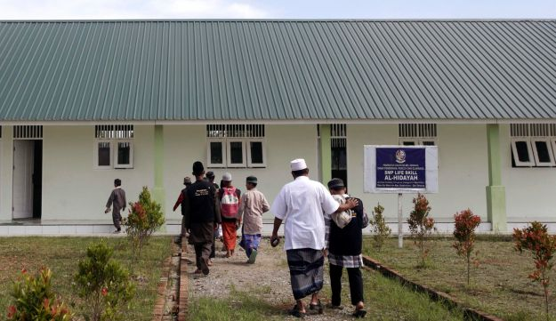 In this July 22, 2017, photo, former radical preacher Khairul Ghazali, center, leads students to a classroom at Al Hidayah Islamic Boarding School, a school he set up for the sons of Islamic militants, in Sei Mencirim, North Sumatra, Indonesia. Ghazali founded the school to prevent the boys, who were ostracized and taunted at mainstream schools, from becoming the next generation of Indonesian jihadists.
