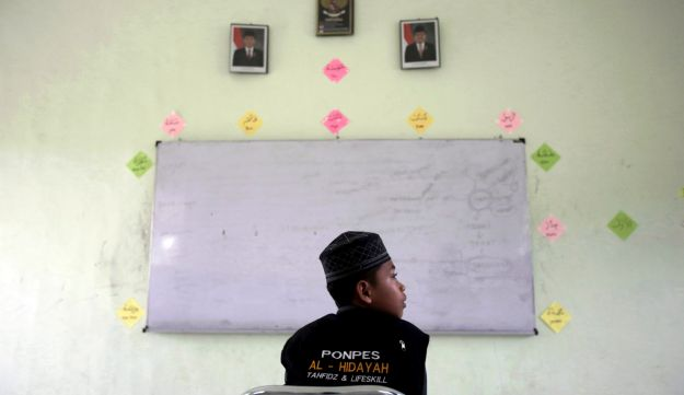 A student sits in a classroom at Al Hidayah Islamic Boarding School in Sei Mencirim, North Sumatra, Indonesia, July 22, 2017. Pupils at the boarding school are the sons of Islamic militants whose fathers were killed in police raids or are in prison for terrorism offenses. Former radical preacher Khairul Ghazali set founded the school to prevent the boys, who were ostracized and taunted at mainstream schools, from becoming the next generation of Indonesian jihadists.