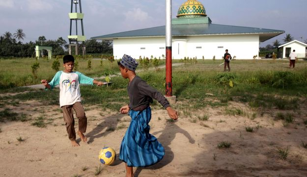 In this July 22, 2017, photo, students play soccer at Al Hidayah Islamic Boarding School in Sei Mencirim, North Sumatra, Indonesia. The school was founded by former radical preacher Khairul Ghazali for the sons of Islamic militants whose fathers are either killed in police raids or in prison for terrorism offenses and aimed at preventing them from becoming the next generation of Indonesian jihadists. (AP Photo/Binsar Bakkara)