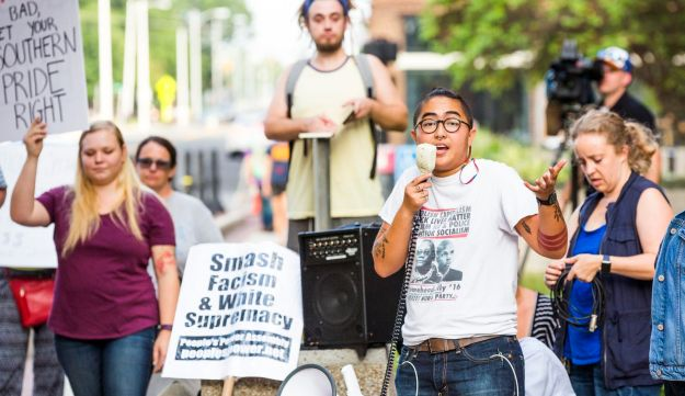 A protest organizer speaks in front of a Confederate statue at the old Durham County Courthouse, Monday, August 14, 2017, in Durham, N.C.
