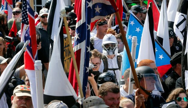 White nationalist demonstrators enter Lee Park surrounded by counterprotesters, Charlottesville, Virginia, August 12, 2017.