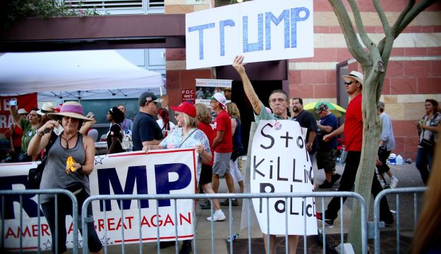 Pro Trump supporters face off with peace activists during protests outside a Donald Trump campaign rally in Phoenix, Arizona on August 22, 2017.