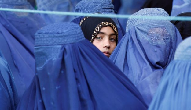 A girl looks on among Afghan women lining up to receive relief assistance, June 11, 2017.