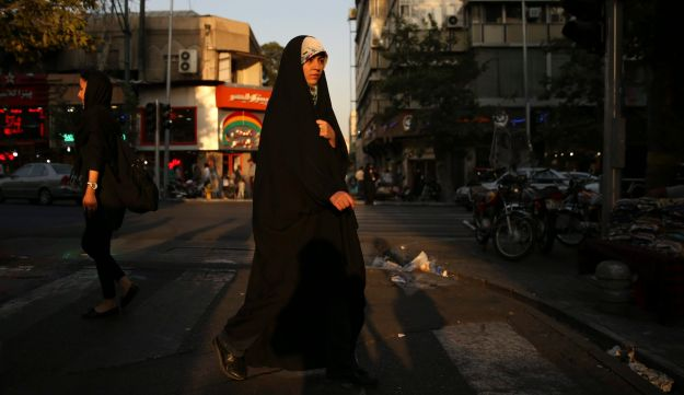 """A woman veiled head-to-toe with the """"chador"""" crosses a street in downtown Tehran, Iran on August 24, 2017."""