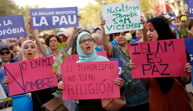"Muslim women hold placards reading (fromL) ""Not in my name"", ""Terrorism doesn't have religion"" and ""Islam is Peace"" during a march against terrorism which slogan will be #NoTincPor (I'm Not Afraid) in Barcelona on August 26, 2017, following the Barcelona and Cambrils attacks killing 15 people and injuring over 100. Tens of thousands of Spaniards and foreigners are to stage a defiant march against terror through Barcelona on August 26 following last week's deadly vehicle rampages. The Mediterranean city is in mourning after a van ploughed into crowds on Las Ramblas boulevard on August 17, followed hours later by a car attack in the seaside town of Cambrils.  / AFP PHOTO / PAU BARRENA"