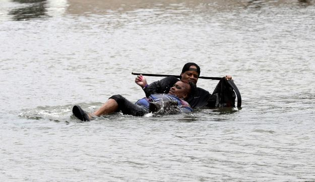 A man helps a woman in floodwaters from Tropical Storm Harvey Sunday, Aug. 27, 2017, in Houston, Texas.