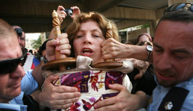 Police escort Women of the Wall leader Anat Hoffman holding a Torah scroll from the Western Wall, on July 12, 2010.