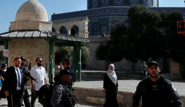 Far right Israeli Rabbi and Israeli parliament member Yehuda Glick (L) walks barefoot, escorted by Israeli police and supporters, inside the flashpoint Al-Aqsa mosque compound, also known as the Temple Mount complex in Jerusalem's Old City on August 29, 2017, after a ban on Israeli lawmakers visiting the ultra-sensitive holy site was lifted for one day.