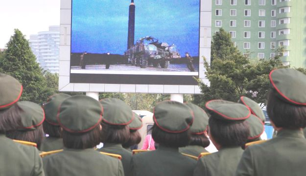 North Koreans in Pyongyang watching a televised news broadcast of the test-fire of an intercontinental ballistic rocket, August 30, 2017.