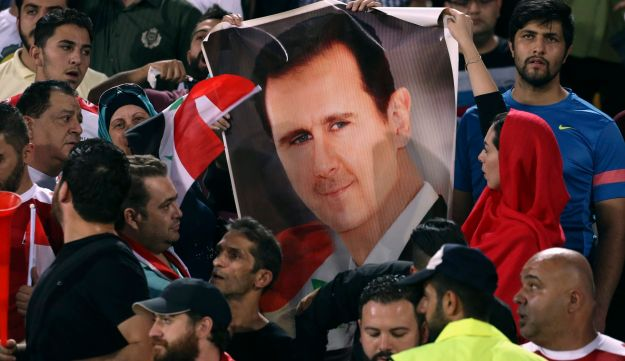 Syrian soccer fans hold a portrait of President Bashar Assad before a match with Iran in a World Cup qualifier, Tehran, September 6, 2017.