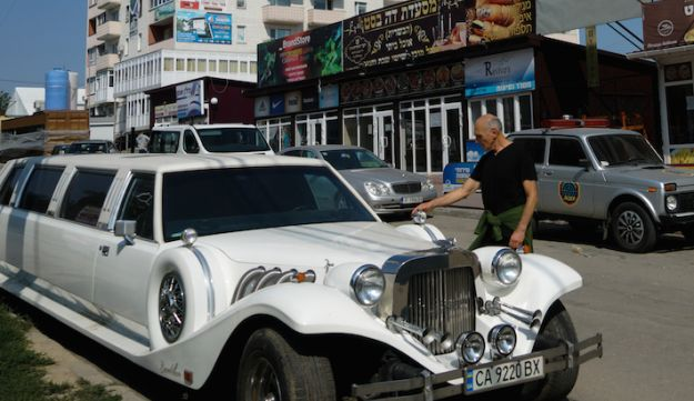 An Israeli visitor to Uman examining a Ukrainian luxury limousine parked on the city's heavily Jewish Pushkin Street, Sept. 8, 2017.