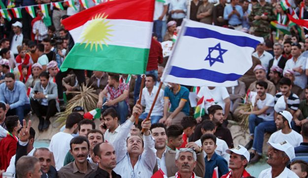 A Kurdish man holds an Israeli and Kurdish flag during a rally to show their support for the upcoming September 25th independence referendum in Erbil, Iraq September 16, 2017.