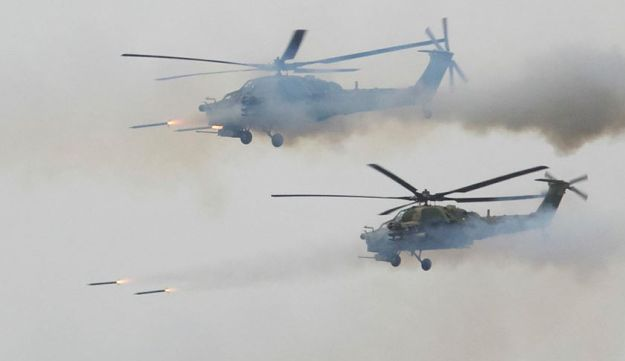 Russian military helicopters fire during a military exercise at a training ground at the Luzhsky Range, near St. Petersburg, Russia, Monday, Sept. 18, 2017