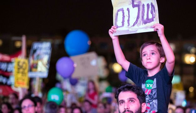 "A young Israeli holds a banner reading ""Peace"" in Hebrew during a mass demonstration against 50 years of occupation titled ""Two States - One Hope"" in Rabin Square, Tel Aviv. May 27, 2017"