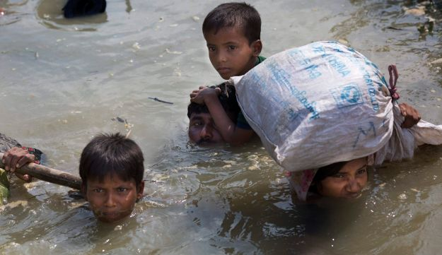 Young Rohingya boys with their family reach the Bangladesh border after crossing a creek of the Naf River on the border with Myanmar