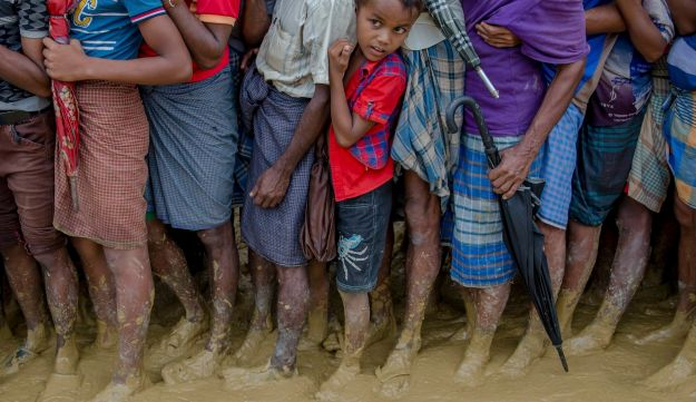 A young Rohingya Muslim boy, who crossed over from Myanmar into Bangladesh, waits alongwith others for his turn to collect food aid near Kutupalong refugee camp, Bangladesh