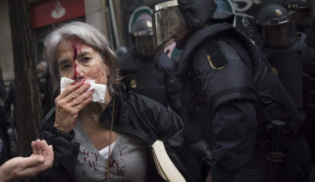 A woman tends to her injuries in front of riot police near a school being used as a polling station for the banned Catalan referendum, Barcelona, Spain, October 1, 2017.