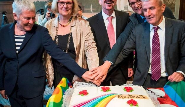 Bode Mende (R) and Karl Kreile (C) cut the rainbow wedding cake with their witnesses Angelika Daser (L), Joerg Steinert (2nd R) and Mayor of Schoeneberg Angelika Schoettler (2nd L) during the wedding ceremony as they are became Germany's first gay couple to be legally married tying the knot at the Schoeneberg town hall in Berlin on October 1, 2017