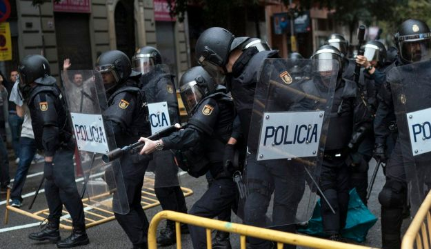 Spanish riot police try to prevent people from reaching a voting site at a school assigned to be a polling station by the Catalan government in Barcelona, October 1, 2017.