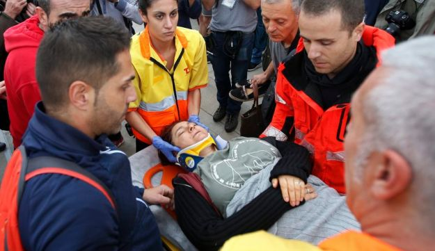 A woman is taken away on a stretcher after getting hurt after civil guards cleared would-be voters in Sant Julia de Ramis, October 1, 2017.