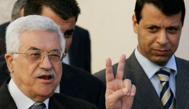 In this Dec. 18, 2006 file photo, Palestinian President Mahmoud Abbas, left, flashes the V sign as then Fatah official, Mohammed Dahlan, looks on in the West Bank town of Ramallah.