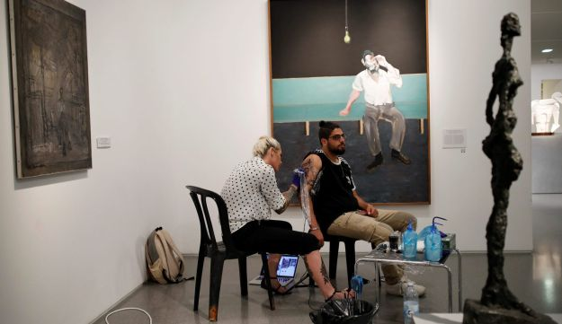 """Yotam Ness, injured while serving as a soldier in the Israeli army, gets a tattoo done by American artist Megan Jean Morris as part of the """"Healing Ink """" project, at the Israel Museum."""