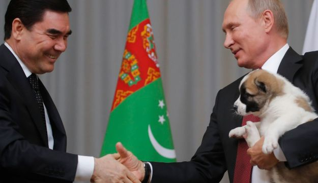 Turkmen President Gurbanguly Berdimuhamedov shakes hands with his Russian counterpart Vladimir Putin after presenting him a Turkmen shepherd dog in Sochi, Russia, October 11, 2017.