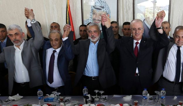 From left to right in front row, Hamas leader in the Gaza Strip Yahya Sinwar, Head of Palestinian General Intelligence Majid Faraj, Head of the Hamas political bureau Ismail Haniya, Palestinian Prime Minister Rami Hamdallah and an Egyptian mediator hold their hands up during a meeting in Gaza City, Monday, Oct. 2, 2017.