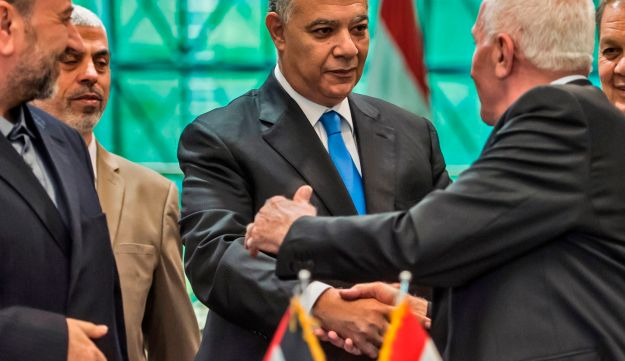 (L to R) Hamas' Saleh al-Aruri, Hamas's leader in the Gaza Strip Yahya Sinwar, Khaled Fawzi, head of the Egyptian Intelligence services, Azzam al-Ahmad, head of the Fatah delegation for the talks, and Fatah's Rawhi Fattouh are pictured following the signing of a reconciliation deal at the Egyptian intelligence services headquarters in Cairo on October 12, 2017, as the two rival Palestinian movements ended their decade-long split following negotiations overseen by Egypt.
