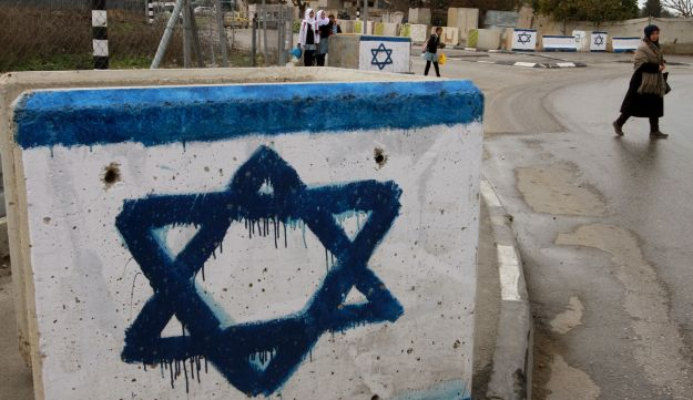 A stone barrier painted with an Israeli flag in Hebron, December 15, 2015.
