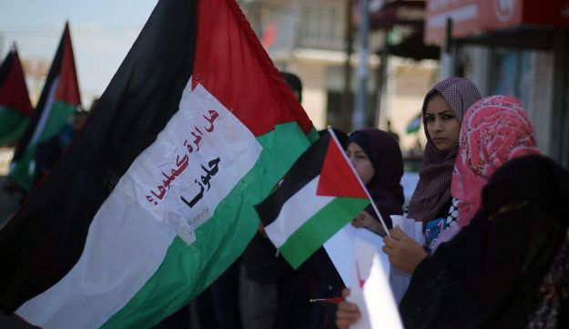 Women holding Palestinian flags after rival Palestinian factions Hamas and Fatah signed a reconciliation deal in Cairo, central Gaza Strip, October 12, 2017.