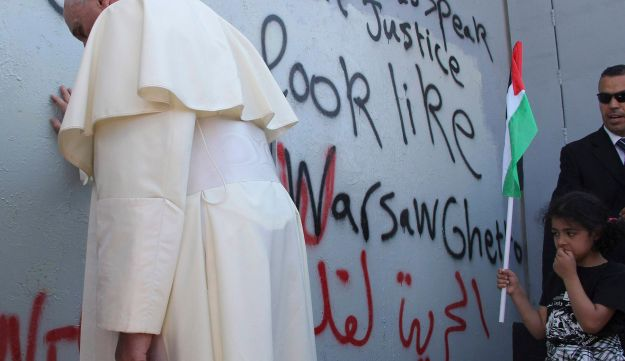 Pope Francis touches the wall that divides Israel from the West Bank, on his way to celebrate a mass in Manger Square next to the Church of the Nativity in the West Bank city of Bethlehem. May 25, 2014