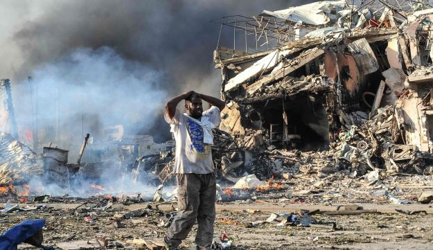 A Somali man reacts next to a dead body on the site where a car bomb exploded at the center of Mogadishu, on October 14, 2017.
