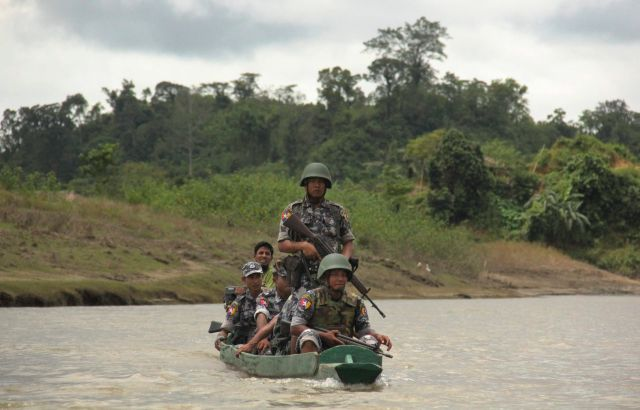 Myanmar Border Guard Police officers travel in a wooden boat operated by Rohingya Muslim men in Rakhine State, Myanmar on July 14, 2017.